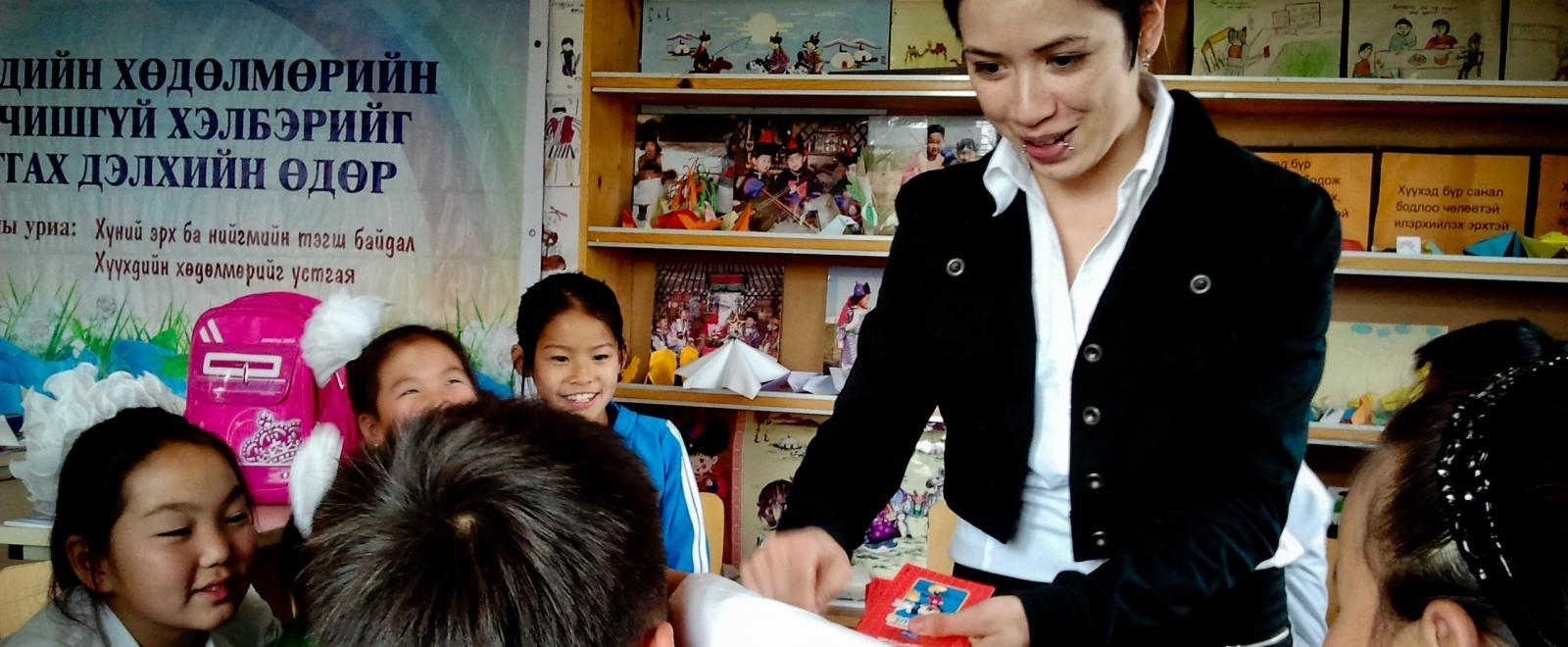 The children play a word game with the volunteer teaching English in Mongolia.